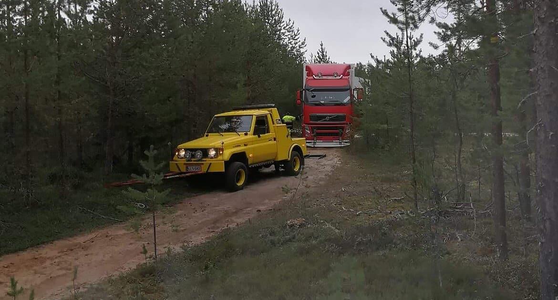 Maasturi hinausauto avustamassa metsätiellä
